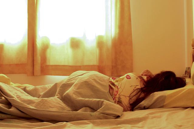 Žena spí v posteli zakrytá paplónom