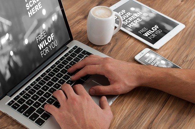 Muž píše na notebooku, vedľa ktorého je smartphone a tablet