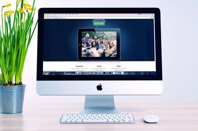 Počítač s fotografiou ľud, vedľa ktorého je kvetináč s narcismi
